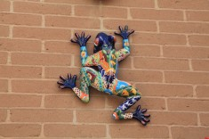 Ceramic critter hanging off a brick wall